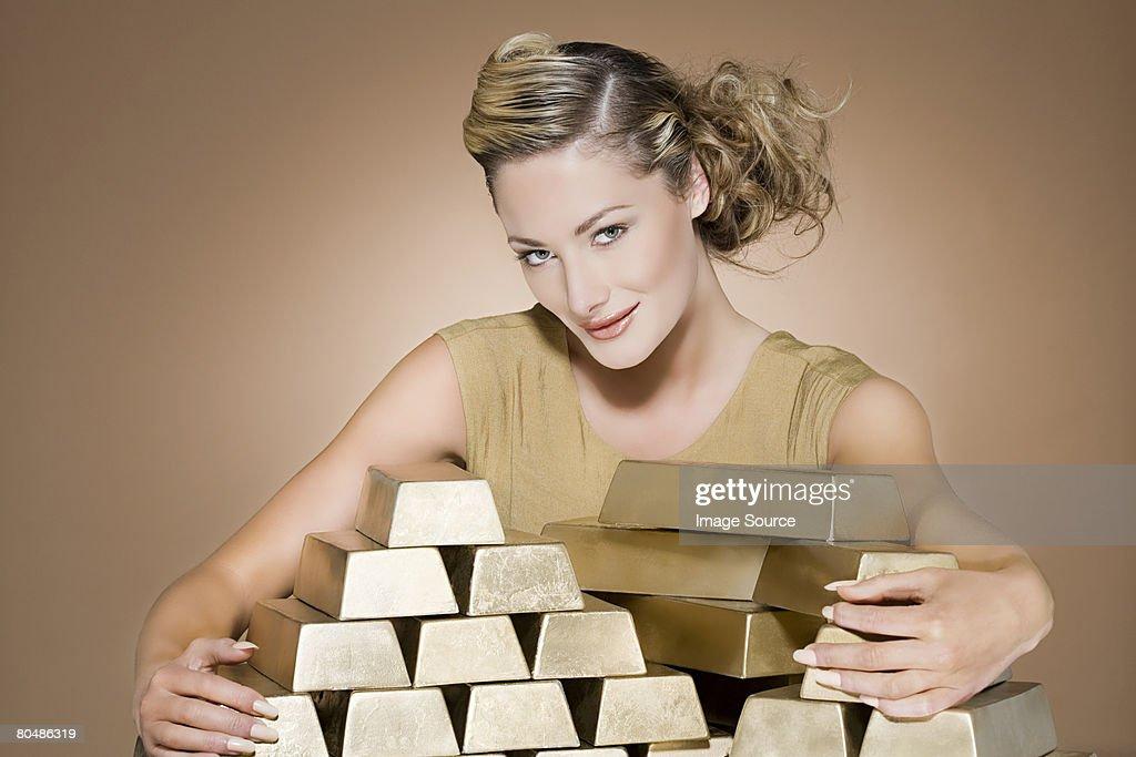 Woman grasping gold bars : Stock Photo