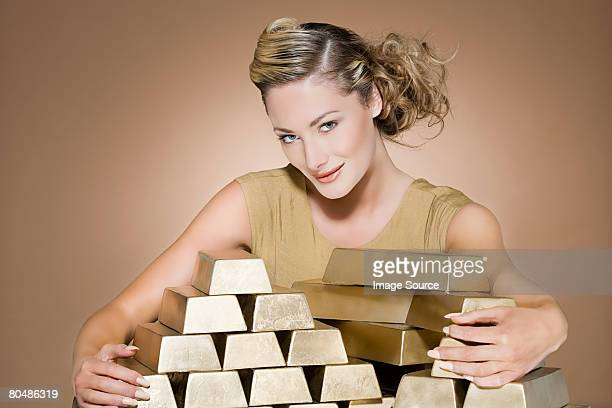 Woman grasping gold bars