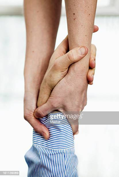 Woman grasping man's wrist, close-up