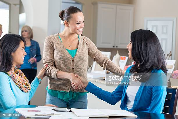 Woman greeting guests at jewelry sale party