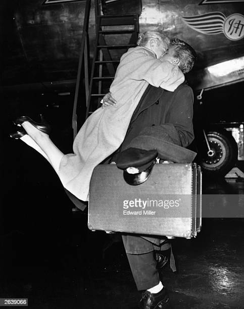 A woman greeting her Skymaster Aircrew husband with enthusiasm after his flight to Albania