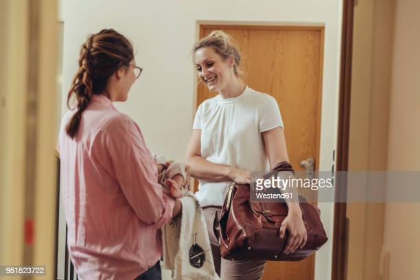 Woman greeting midwife at her home's apartment door