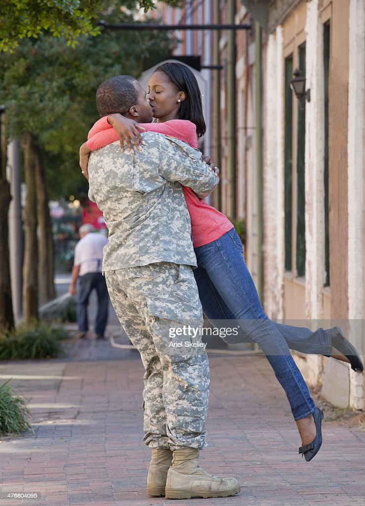 Woman greeting returning soldier : Stock Photo