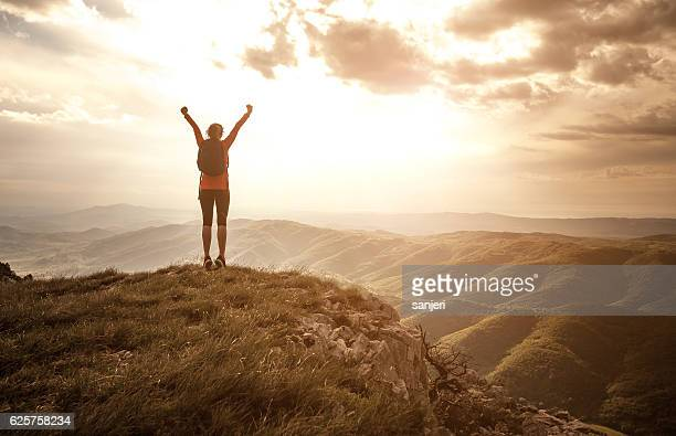 woman greeting the sun on the top of the hill - hill stock pictures, royalty-free photos & images