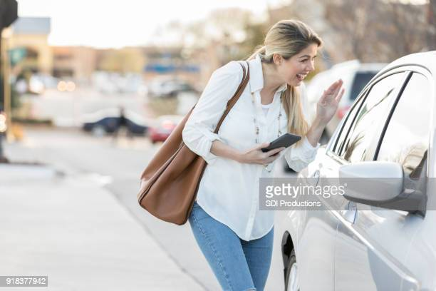 woman greets ride share driver - car pooling stock photos and pictures