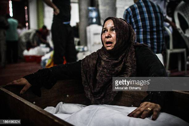 CONTENT] A woman grieve next to a coffin at Iman mosque which was turned into a makeshift morgue following the violent dispersal of Rabaa Adaweya...