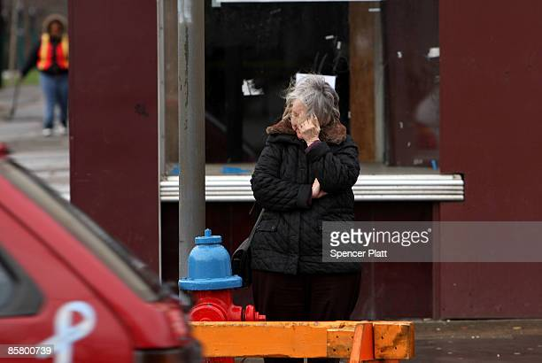 Woman grieves across the street from the site where a gunman killed 13 people in an immigration community center yesterday April 4, 2009 in...