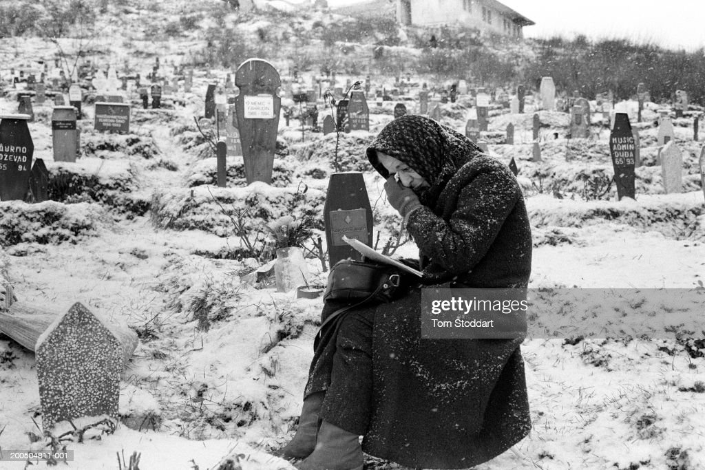 Bosnia, Sarajevo - January 1995. A woman grieves at the grave of her son in a snow covered Sarajevo cemetery. During the 47 months between the spring of 1992 and February 1996, the people of Sarajevo endured the longest siege Europe has witnessed since the end of the Second World War. More than 10,600 people were killed with a further 56,000 wounded or maimed.