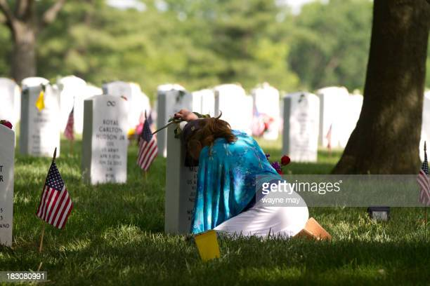 Woman grieves at the grave site of her husband.