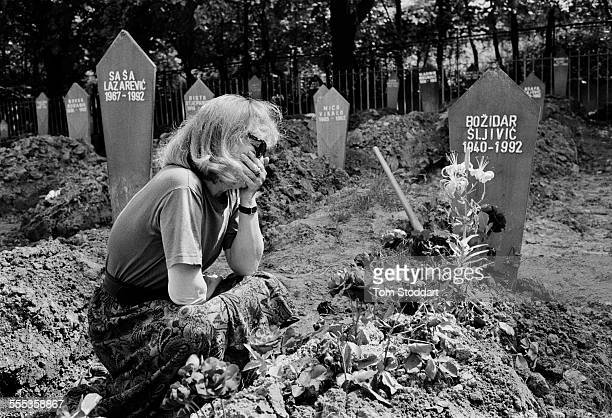 A woman grieves by a grave in the Lion Cemetery Sarajevo She was later identified as Behireta Sljivic whose soldier husband was killed during the war...