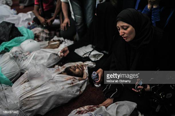 Woman grieves next to dead bodies laid at Iman mosque which was turned into a makeshift morgue following the violent dispersal of Rabaa Adaweya...