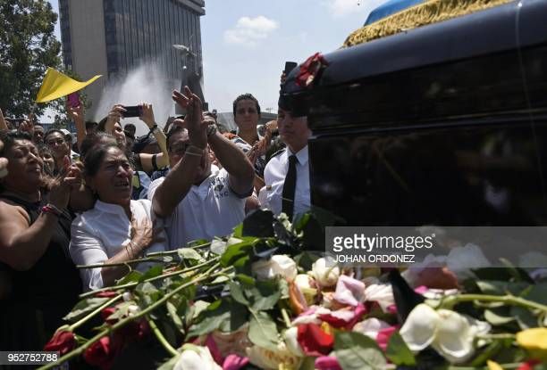 Woman grieves next to the frag-draped coffin of Guatemala City Mayor and former Guatemalan President Alvaro Arzu, during his funeral as they arrive...