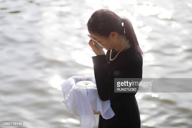 woman grieving with funeral urn - urn stock pictures, royalty-free photos & images