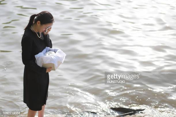 woman grieving with funeral urn - 火葬 ストックフォトと画像