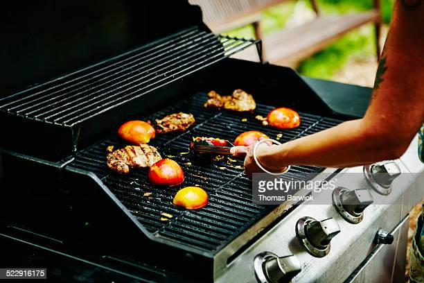 Woman grilling nectarines and chicken on barbecue