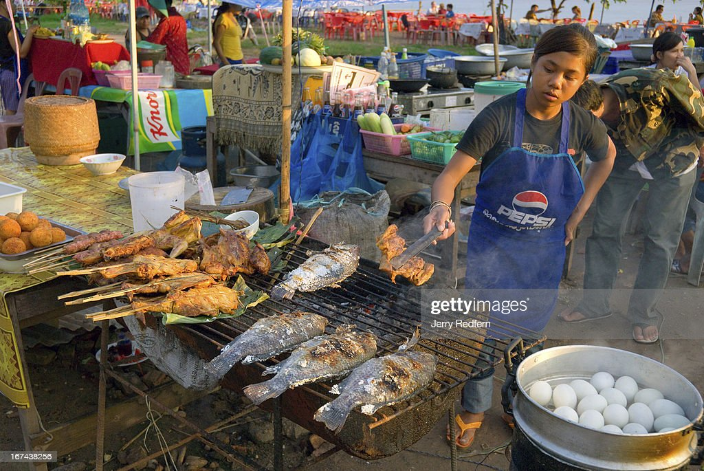 A woman grills chicken and fish at a food stall along the Mekong river front. Everyday small restaurants pop up along the river front selling grilled foods and beer and drawing hundreds of locals and foreign tourists to watch the sun set and the evening fall on the capital..