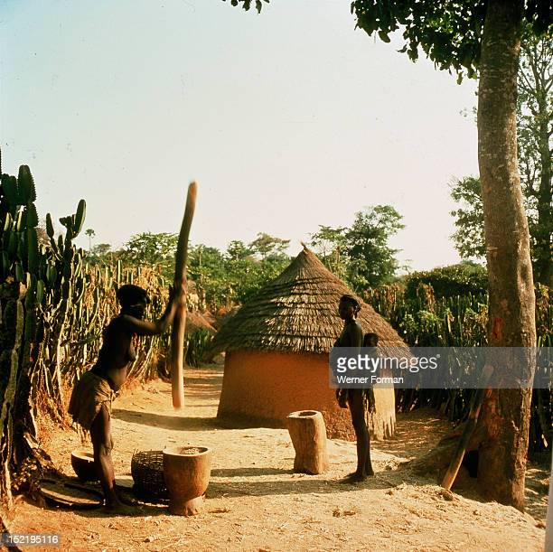 A woman grinding millet with a pestle and mortar in a Miango village near Jos Nigeria Miango late 1950's early 1960's Jos plateau