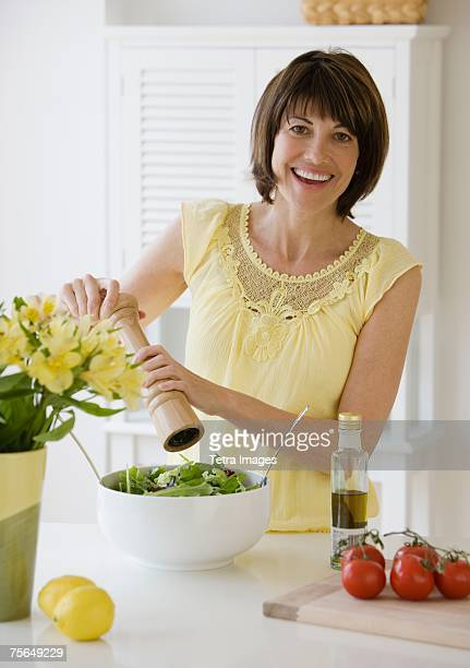 woman grinding pepper onto salad - pepper mill stock pictures, royalty-free photos & images