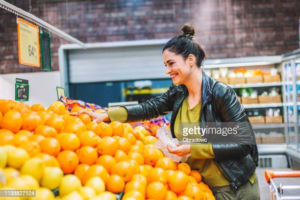 woman groceries shopping - orange fruit stock pictures, royalty-free photos & images