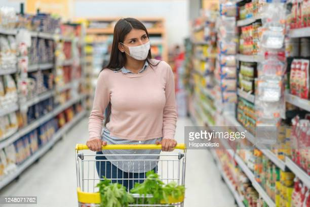 woman grocery shopping at the supermarket wearing a facemask and pushing the car - biosecurity stock pictures, royalty-free photos & images