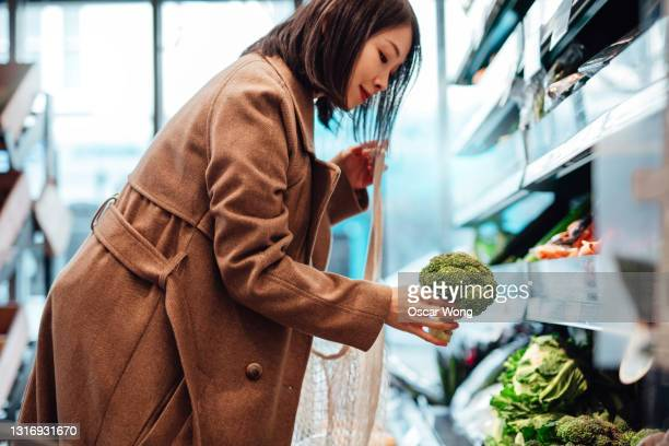 woman grocery shopping for fresh organic vegetables in supermarket - crucifers stock pictures, royalty-free photos & images