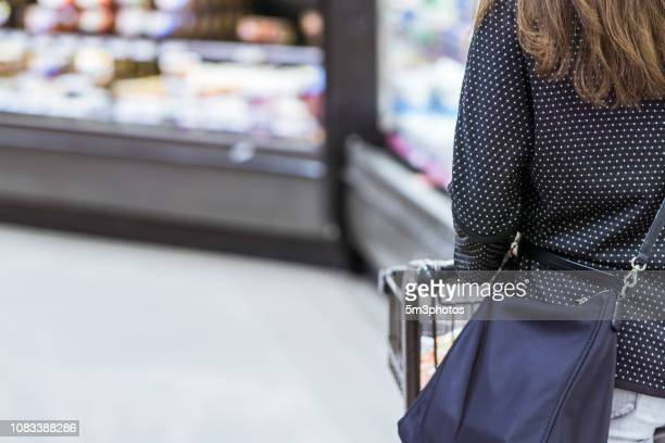 woman grocery shopping in store supermarket aisle - food staple stock pictures, royalty-free photos & images