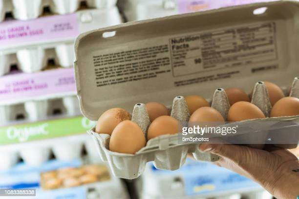 woman grocery shopping in store supermarket aisle - carton stock pictures, royalty-free photos & images
