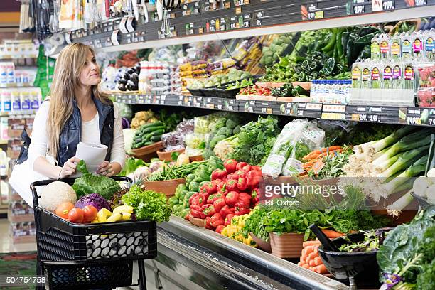 woman grocery shopping - produce aisle stock photos and pictures