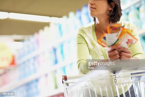 woman grocery shopping - coupon stock photos and pictures