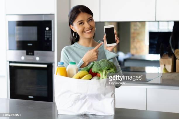 woman grocery shopping via mobile application - software foto e immagini stock