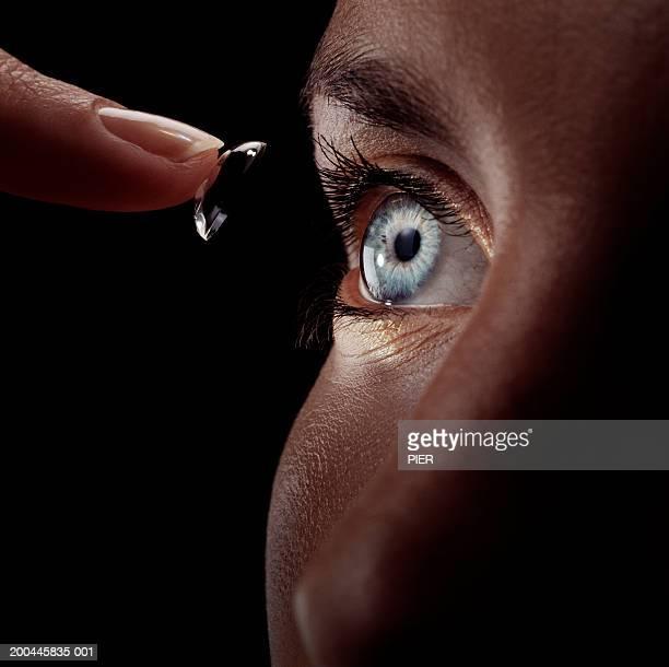 Woman guiding contact lens into eye, close-up