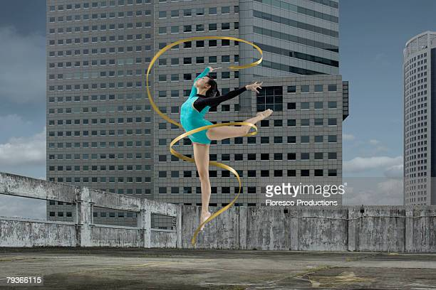 woman gymnast outdoors on rooftop jumping in air with ribbon - rhythmic gymnastics stock pictures, royalty-free photos & images