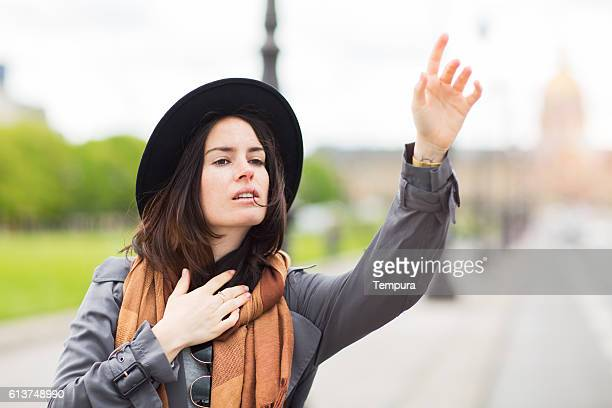 Woman hailing a taxi in the streets of Paris