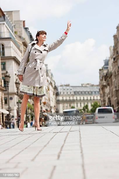 Woman hailing a taxi, Paris, Ile-de-France, France