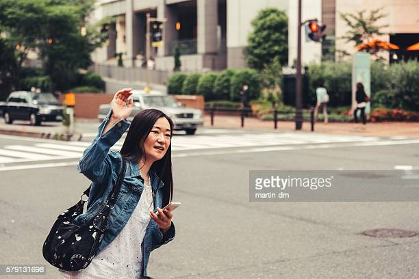 Woman hailing for Uber in Osaka