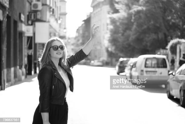 Woman Hailing Taxi On Street In City