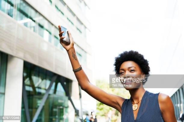 Woman hailing taxi with mobile