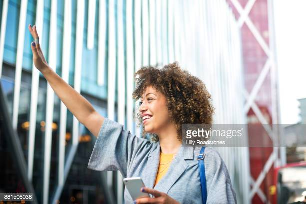 Woman hailing taxi with phone