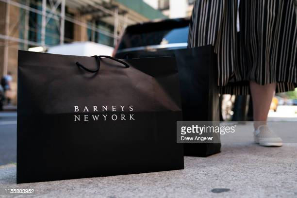 A woman hails a cab as she rests her Barneys New York shopping bags on the curb outside of the store in Midtown Manhattan July 15 2019 in New York...