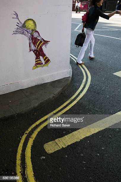 A woman hails a taxi in a London street that has been visited by the cartoon graffiti street artist Nathan Bowen of fireman created outside...