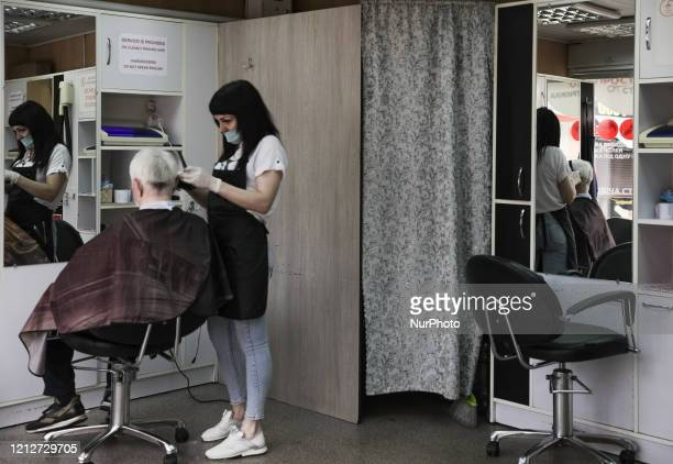 A woman haircuts her client in a barbershop in Kyiv Ukraine May 11 2020 Ukraine allows to visit parks squares recreation areas and open some...
