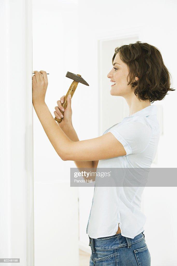Woman hammering nail into wall, smiling : Stock Photo