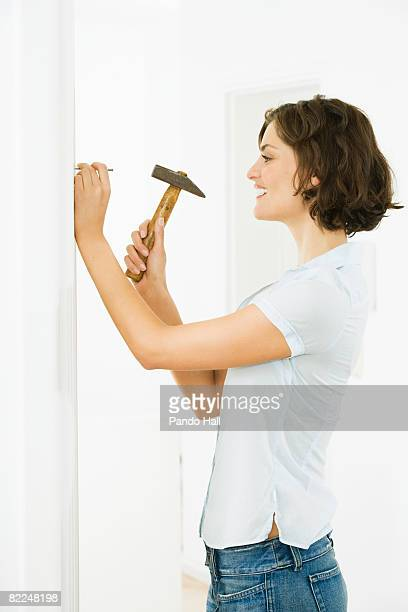 Woman hammering nail into wall, smiling