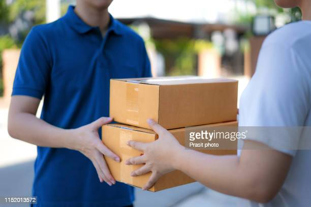 woman hand accepting a delivery of boxes from deliveryman in house. - 受ける ストックフォトと画像