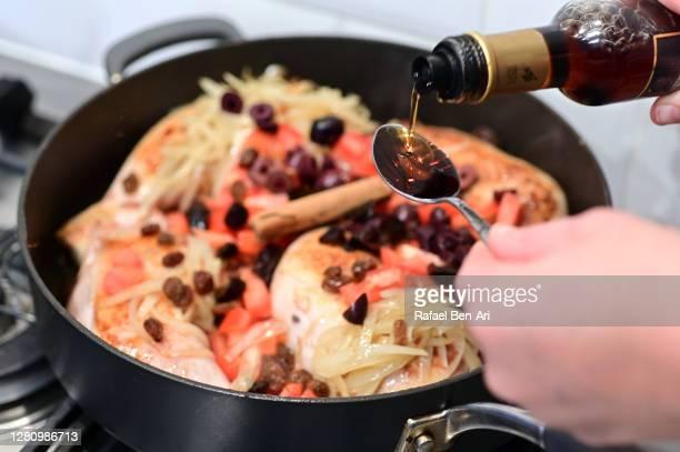 woman hand adding sherry vinegar to a spanish chicken dish - rafael ben ari fotografías e imágenes de stock