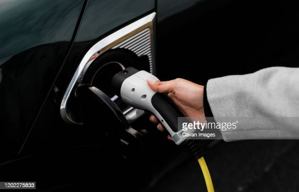 woman hand and socket plugging in an electric car - electric car stock pictures, royalty-free photos & images