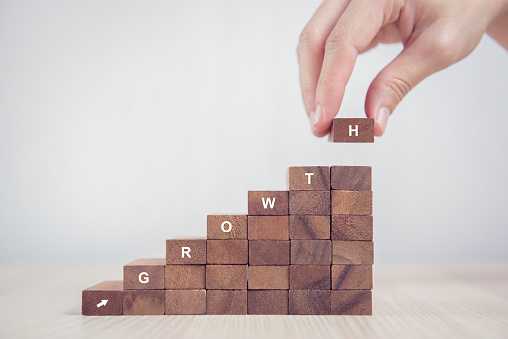 Woman hand arranging wood block stacking as step stair. Business concept growth success process. 910360514