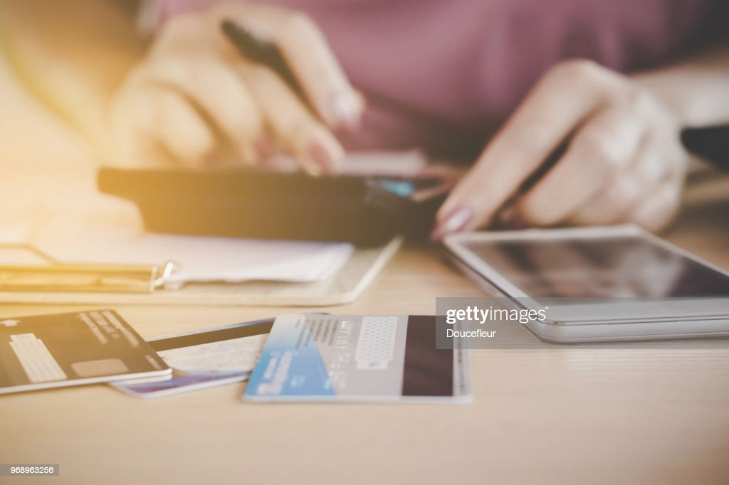 woman hand calculating her expenses and debt from credit cards with smart phone : Stock Photo