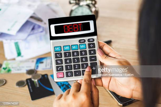 woman hand calculating her expenses with unpaid financial bills ,credit cards on desk - eyeem collection stock pictures, royalty-free photos & images