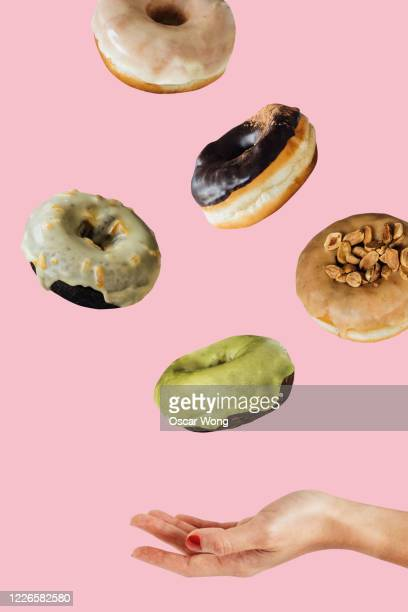 woman hand catching donuts flying on a pink coloured background - cake stock pictures, royalty-free photos & images